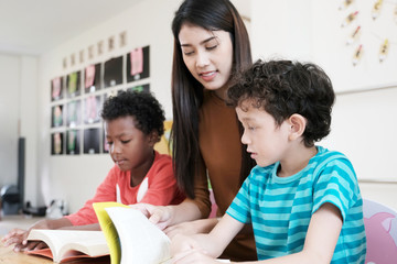 Young asian woman teacher and American, African boys in kindergarten classroom, preschool education concept