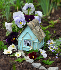 Small fairy house with viola and daisy flowers in the garden. Lovely miniature house for greeting cards, wedding or birthday concept, real estate, downsizing, home ownership. Vintage summer background