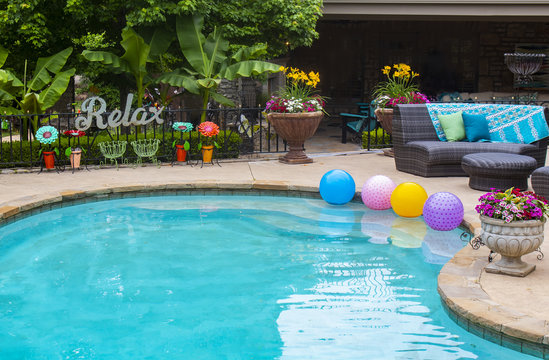 Relax by the pool - flowers and plants and decor by the pool with a big RELAX metal sign on the fence and multi-colored balls floating