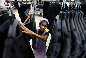 A woman hangs dresses at Timex garments factory in Wattala