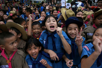 Students celebrate in front of Chiang Rai Prachanukroh hospital, where the 12 soccer players and their coach rescued from the Tham Luang cave complex are being treated, in Chiang Rai