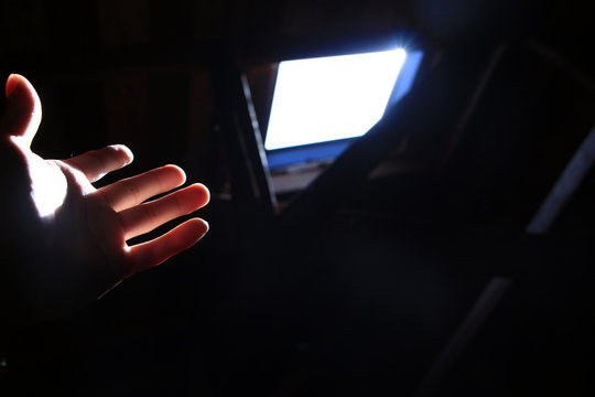 Hand reaching out for the light from a ceiling window