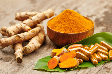 Turmeric powder in wooden bowls and turmeric capsules on wooden background