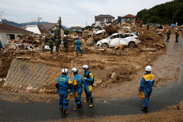 Rescue workers and Japan Self-Defense Force soldiers search for missing people at a landslide site after heavy rain in Kumano Town