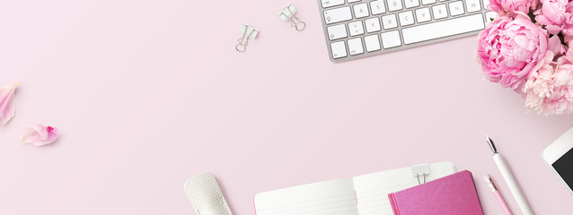 feminine banner or shop header with office / writing supplies, technical gadgets, smartphone and a bunch of pink flowers on a pink background - copyspace for your text and  branding - top view Wall mural