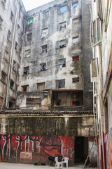 Low angle view of an internal pavilion of a ruined building with shabby walls with graffiti occupied by social housing movement as home for poor people. San Paolo. Brazil. South America. No people.
