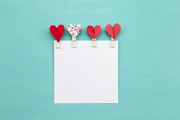 Red heart clip design with blank white paper on blue background
