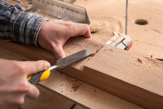 Close up of young  man builder wearing in a plaid shirt   treating a wooden product with a chisel in the workshop, close-up