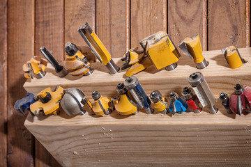 Close-up of a large set of metal drills for a hand drill for drilling wood on a wooden table in the workshop