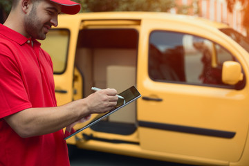 Man in red signs delivery on touchscreen tablet. Cropped shot of man wearing red shirt signing tablet for delivery. Yellow car in background.