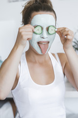 Young Pretty Blonde woman with facial mask posing with cucumber at home. Wellbeing concept, Morning skin care routine.