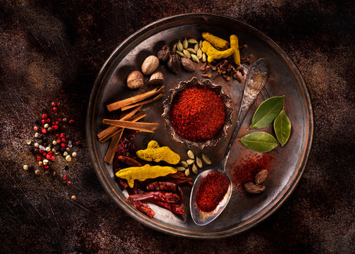 Indian spices and herbs on a plate on a dark concrete background