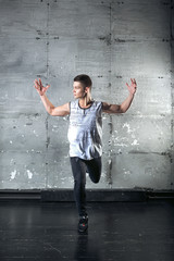 Handsome man dancer dancing in studio with gray background