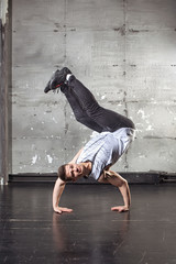 Handsome man dancer dancing. Man stands on hands in a dance pose.