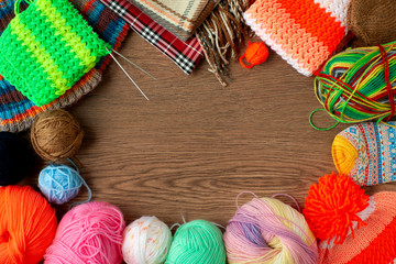 Yarn, needles and knitted clothes. View from above. Multicolored balls of yarn for knitting on a wooden background. Knitting and coziness.
