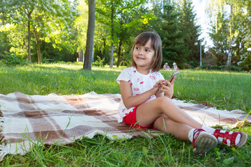 The little girl playing with a smartphone in the open air.