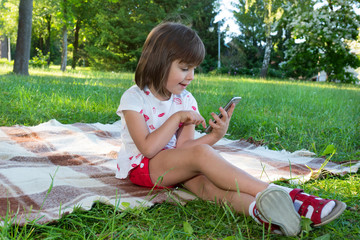The girl in the park, texting on the cell phone in the open air.