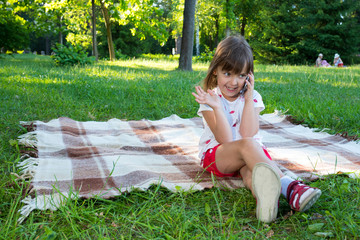 The happy girl sitting on the blanket, talking over the phone.