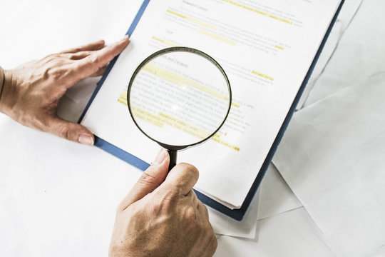 Legal team checking the fine print on business contract to analyze terms and conditions and sign.