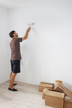 Young cute guy with a beard in a striped T-shirt and blue shorts is painting a white wall in an apartment on a mortgage in a new building.