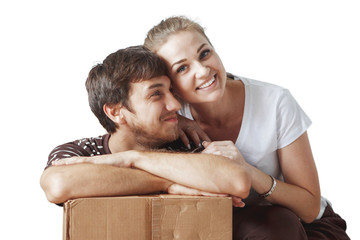 Young cute couple just married sitting on floor in a new apartment after repair among the cardboard boxes are happy and smiling.