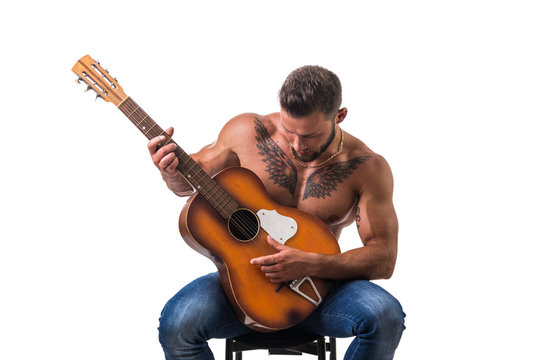 Portrait of muscular man with tattoo playing guitar. Isolated on white background