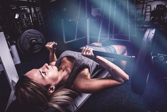 Woman training on bench press