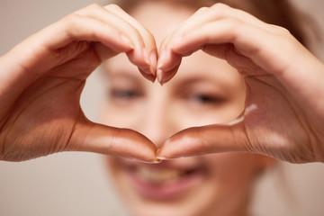 Hände formen Herz als Zeichen der Liebe