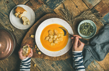 Flat-lay of female hands and Fall warming pumpkin cream soup in plate with croutons and seeds over rustic wooden background, top view. Autumn vegetarian, vegan, healthy comfort food eating concept