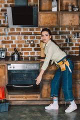 shocked young repairwoman opening broken oven with smoke inside