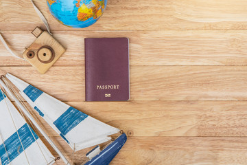 Preparation for Traveling concept, passport, sailboat , camera wood ,Globe sphere orb model , on a vintage wooden background with copy space.Traveling background concept.
