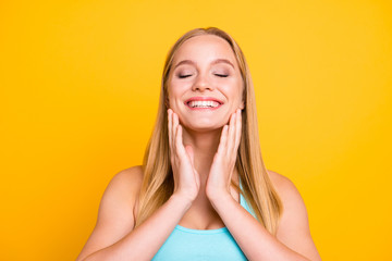 Young charming blonde girl closes her eyes with joy and touches her cheeks with her hands against yellow background