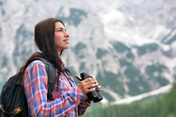 Portrait of a beautiful woman (girl) while she is looking at the mountains. Concept: Holiday, travel, happiness, freedom