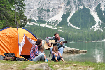 Poster Camping Portrait of a happy family while they are having a good day at the lake. Concept: Love, holiday, music