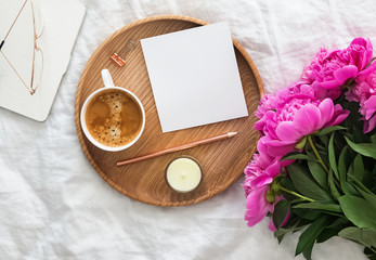 Coffee, pink peonies and blank paper on the bed