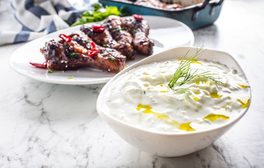 Greek dip sauce or dressing tzatziki with chicken legs