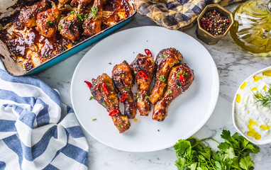 Grilled roasted and barbecue chicken legs on white plate.