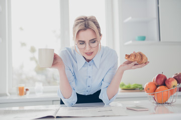 Young elegant lovely charming clever attractive adorable smiling woman office executive worker wearing spectacles reading newspaper early in the morning having a drink and croissant in kitchen