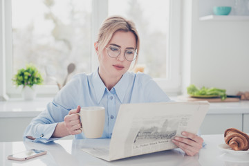 Adult adorable woman office executive worker wearing eye-glasses keeping in hands and reading newspaper early in the morning having a drink with croissant in light kitchen