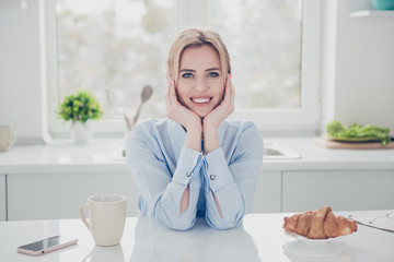 Young adorable beautiful woman office executive worker wearing light blue shirt early in the morning having a drink and croissant in kitchen. Pink smartphone lying on white table