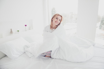 Young cute adorable attractive smiling blonde woman awakening in bed on white sheets covered wrapped in blanket wearing pajama enjoying in bedroom with white interior