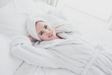 Young cute adorable attractive mature smiling woman lying in bed on white sheets and pillow wearing bathrobe and turban enjoying in bedroom. Top above high angle veiw