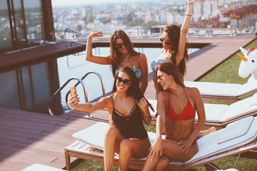 Four young women in a penthouse on sun chairs near the pool  have fun