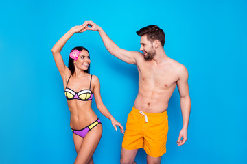Slow summer dance! Happy handsome man with yellow shorts spin charming woman in colourful swimwear and flower on here hair. Joyful happy gay turn her girlfiends waist, isolated on blue background