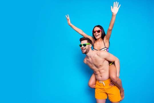 Handsome man wear in summer glasses and yellow shorts keep on back charming young woman holding hands to side making airplane isolated on blue background