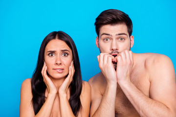 Close up of scared woman and man with naked shoulders. Couple look at the camera and touching mouth by hands. Concept of human emotions isolated on blue background