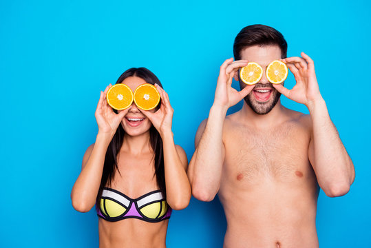 Cheerful young woman ang attractive muscles guy holding two halves of orange and lemons near eyes isolated on blue background. Healthy summer concept