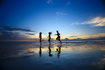 silhouettes of athletes running along the beach / sports summer in the warm sea, healthy rest, sports activity, summer vacation