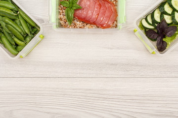 Plastic meal prep containers with fresh green peas, boiled buckwheat porridge and slices of meat, cucumbers and salad