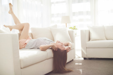 Cheerful young Chinese woman relaxing on sofa